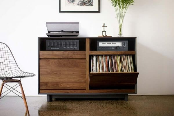 AERO 51 LP Media Storage Cabinet made from North American hardwood. Features 2 flip-style record storage bins with room for 120 LPs each. The top drawers include two hi-fi audio consoles. Features a Walnut finish with a dark grey exterior and is sitting in a living room setting.