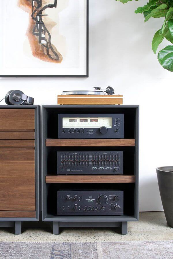 AERO Audio Rack Walnut that is 3 shelves high with hi-fi audio equipment on each shelf and a Modern Record Player on top. It features a dark black exterior finish and is sitting in a living room setting.