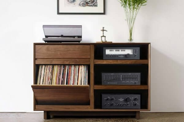 AERO 51 LP Storage Console made from North American hardwood. Features a flip-style record storage bins with room for 120 LPs. The right side drawers have room for 3 hi-fi audio equipment as well as the top shelf and includes a turntable on top. It features a Walnut finish and is sitting in a living room setting.